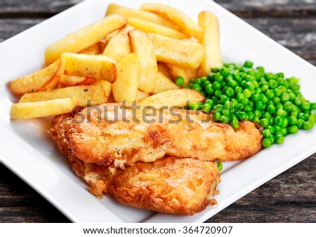 British Traditional Fish and chips with peas. - stock photo