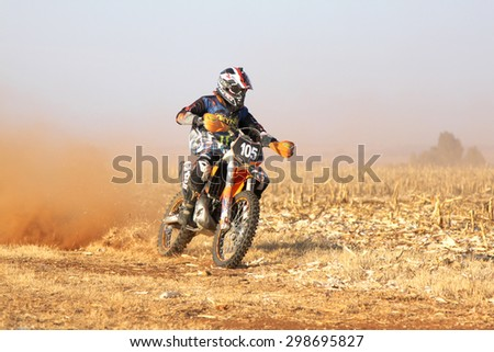BRITS, SOUTH AFRICA - July 11:  Africa-Offroad Racing Rally,  on July 11, 2015 at Koster, North West Province, South Africa.  Motorbike kicking up trail of dust on sand track during rally race.  - stock photo