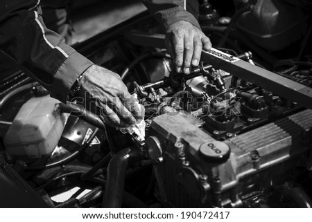 BRNO, CZECH REPUBLIC - APRIL 27, 2014: Mechanic's hands work on an vintage engine during Histo Cup Austria racing event at Brno Circuit. - stock photo