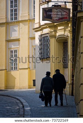 BRNO, CZECH REPUBLIC - MARCH 5: Old couple walking in Dominiknsk Street, in the town of Brno on March 5, 2011. Brno is the second largest city in the Czech Rep. and a very popular tourist destination. - stock photo