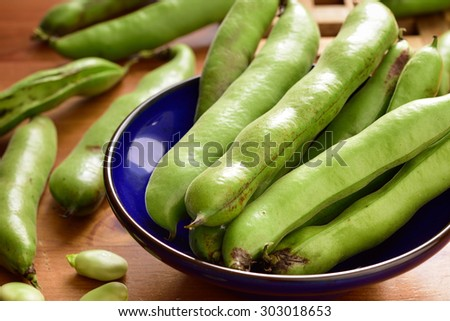 Broad beans fava beans in bowl on wooden table. Summer vegetables, legumes. Angle view. - stock photo
