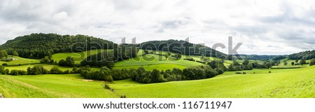 Broad panorama of the countryside in North Wales with green field in foreground - stock photo