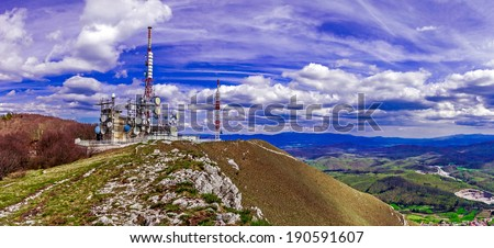 Broad perspective of a remote mountain communications center with different antennas and towers against a deep blue sky with beautiful white clouds on top of the Nanos, Slovenia  - stock photo