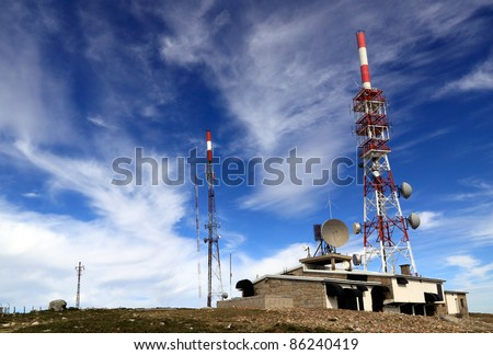 Broad perspective of a remote mountain communications center with different antennas and towers against a deep blue sky with beautiful white clouds - stock photo