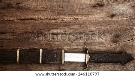 Broad sword on wooden background - stock photo