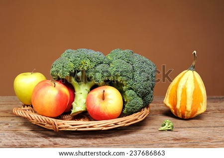 Broccoli, apples and decorative pumpkins on the table - stock photo