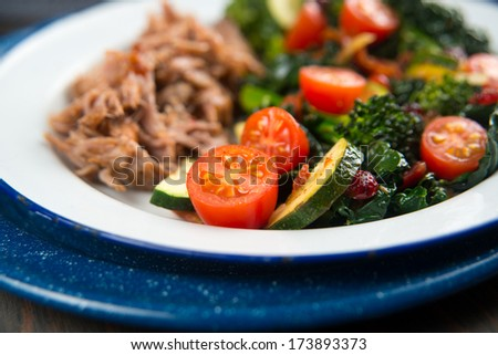 Broccoli, Cherry Tomatoes, Italian Kale, and Onions Sauteed in Skillet for Healthy Meal Served with Slow Cooked Pulled Pork - stock photo