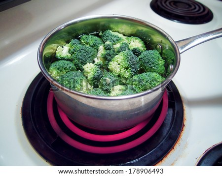 Broccoli in a pot cooking on a hot burner - stock photo