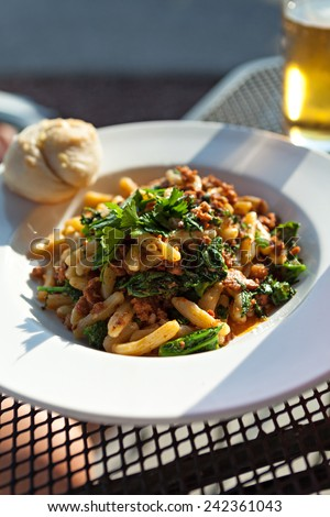 Broccoli rabe dish with sausage over penne pasta presented in a white dish. - stock photo