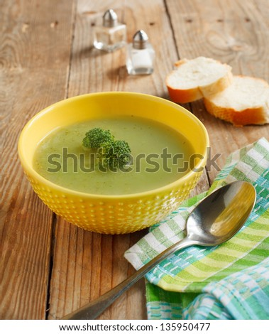 Broccoli soup in bowl over wood background - stock photo