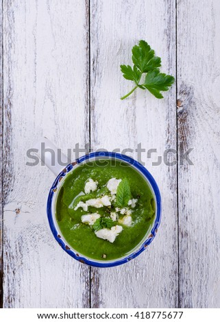 Broccoli soup with mint and feta cheese on white wooden backgrou - stock photo