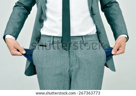 broke businessman wearing a gray suit showing his empty pockets - stock photo