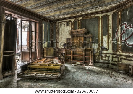 Broken and vandalized piano in an abandoned manor, HDR processing - stock photo