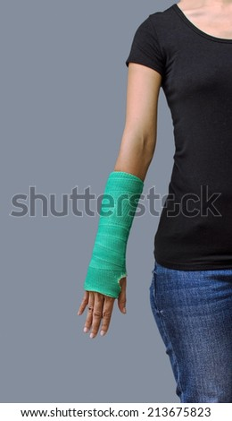 broken arm with green cast on glay background. - stock photo