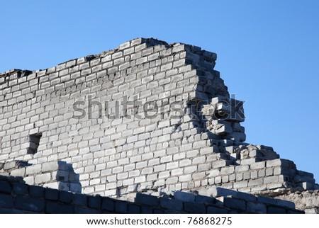 Broken brick wall made of gray brick against the blue sky - stock photo