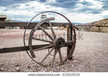 Broken cart wheel on wild west with blue sky - stock photo