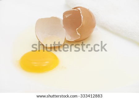 Broken chicken egg and brown shell exposing the raw yellow yolk and white on a white place.  White kitchen towel at background.  - stock photo