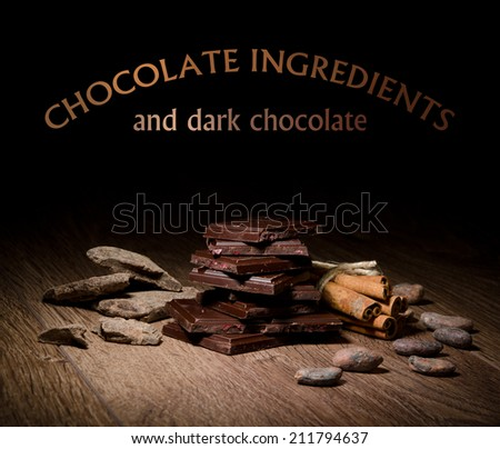 Broken chocolate bar and spices on wooden table. - stock photo