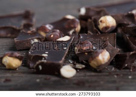 Broken chocolate bar  on wooden table. Selective focus - stock photo