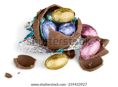 Broken chocolate Easter egg wrapped in pink foil with colorful candies on white background  - stock photo