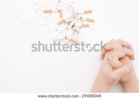 Broken Cigarettes and Folded Hands - stock photo