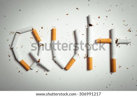 Broken cigarettes arranged as a word quit - stop smoking concept - stock photo