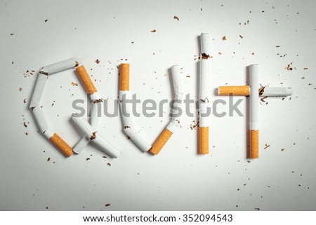 Broken cigarettes arranged as a word quit - stop smoking concept - stock photo