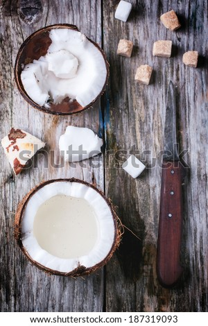 Broken coconut with coconut milk, sugar cubes and vintage knife on old wooden background. Top view - stock photo