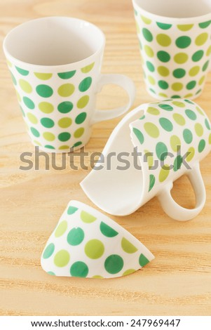 Broken cup of tea with two whole. Selective focus - stock photo