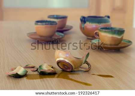 Broken  cup with spilled coffee on a table with cups. - stock photo