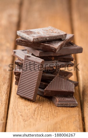 Broken dark chocolate bar on a old wooden table - stock photo