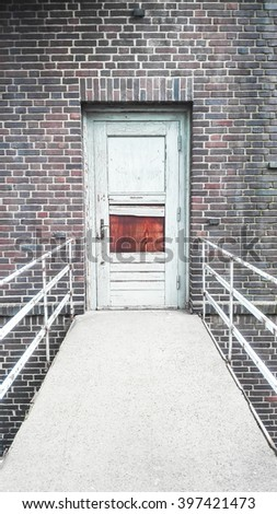 Broken door and handrail in an old black brick stone building - stock photo