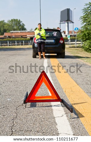 Broken down car with red warning triangle - stock photo