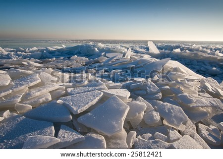 broken drifting ice at shore of frozen dutch lake - stock photo