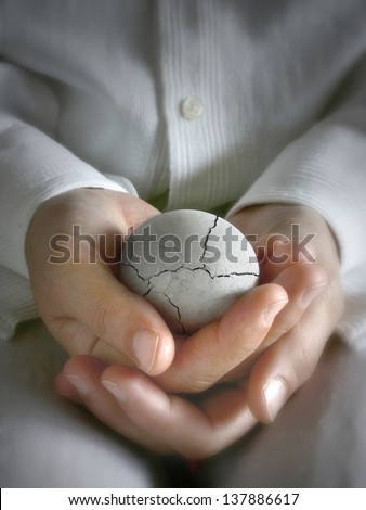 Broken egg in the hands - stock photo