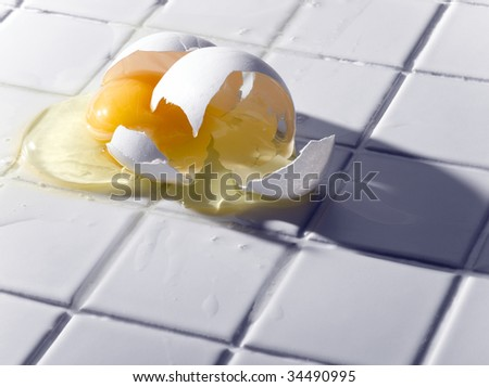 Broken egg on white tiles - stock photo