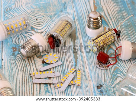 broken energy saving lamps, wires on a blue background - stock photo
