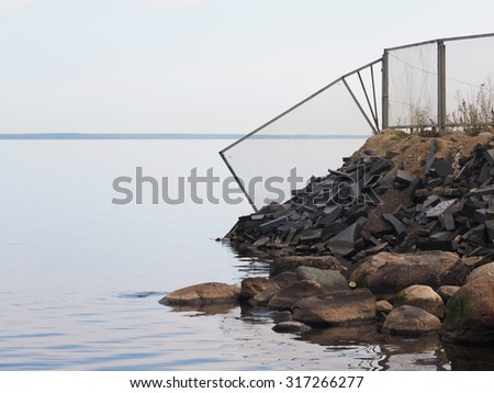 broken fence by the lake - stock photo