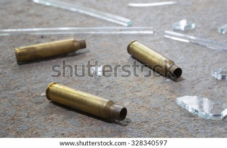 Broken glass and rifle brass that are on concrete - stock photo