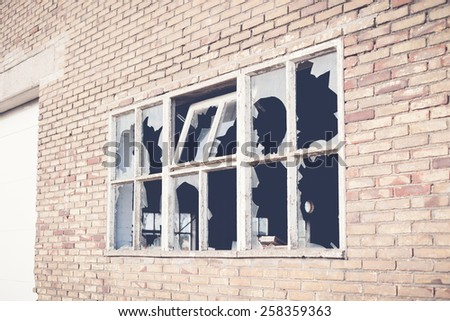 Broken glass at Window of old industrial urbex building - stock photo