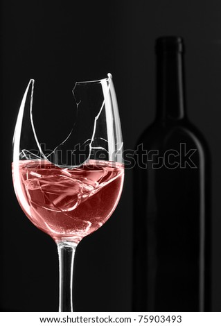 Broken glass of red wine with bottle on background - stock photo