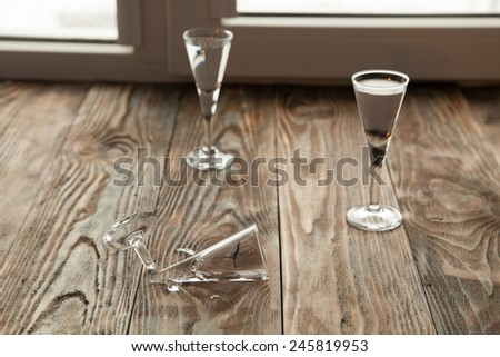 Broken glass on the wooden table - stock photo