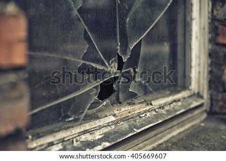 broken glass window reflecting clounding sky - stock photo
