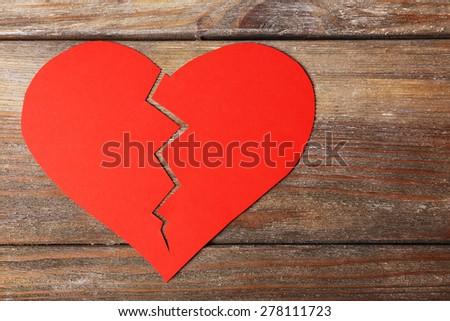 Broken heart on wooden planks background - stock photo