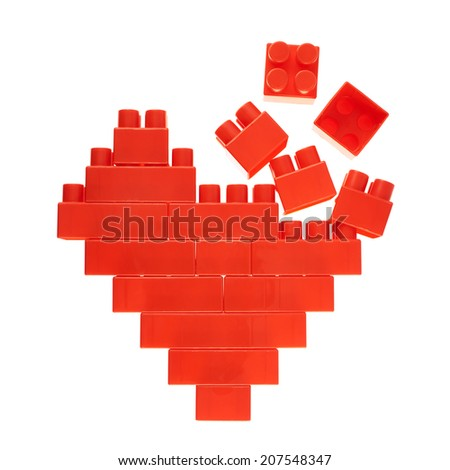 Broken heart symbol made of red plastic toy construction bricks isolated over the white background - stock photo