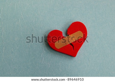 broken heart with a bandage, on blue - stock photo
