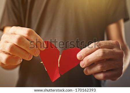 Broken hearted man. Valentines day concept. Man holding broken heart in his hands - stock photo
