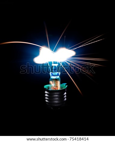 Broken Light bulb burning in dark - stock photo