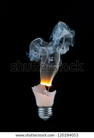 Broken light bulb burns and smoke from it on a black background - stock photo