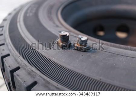 Broken mount screws lying on truck tire - stock photo